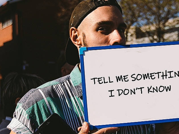 "A person wearing a tshirt and backwards-facing cap holding a whiteboard in front of their mouth that says ""Tell me something I don't know"""
