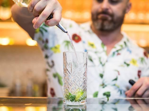 Man pouring spirit into mojito glass