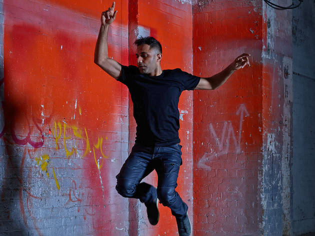 A man in black t-shirt and jeans jumps with one finger in the air in front of a red spray-painted warehouse brick wall