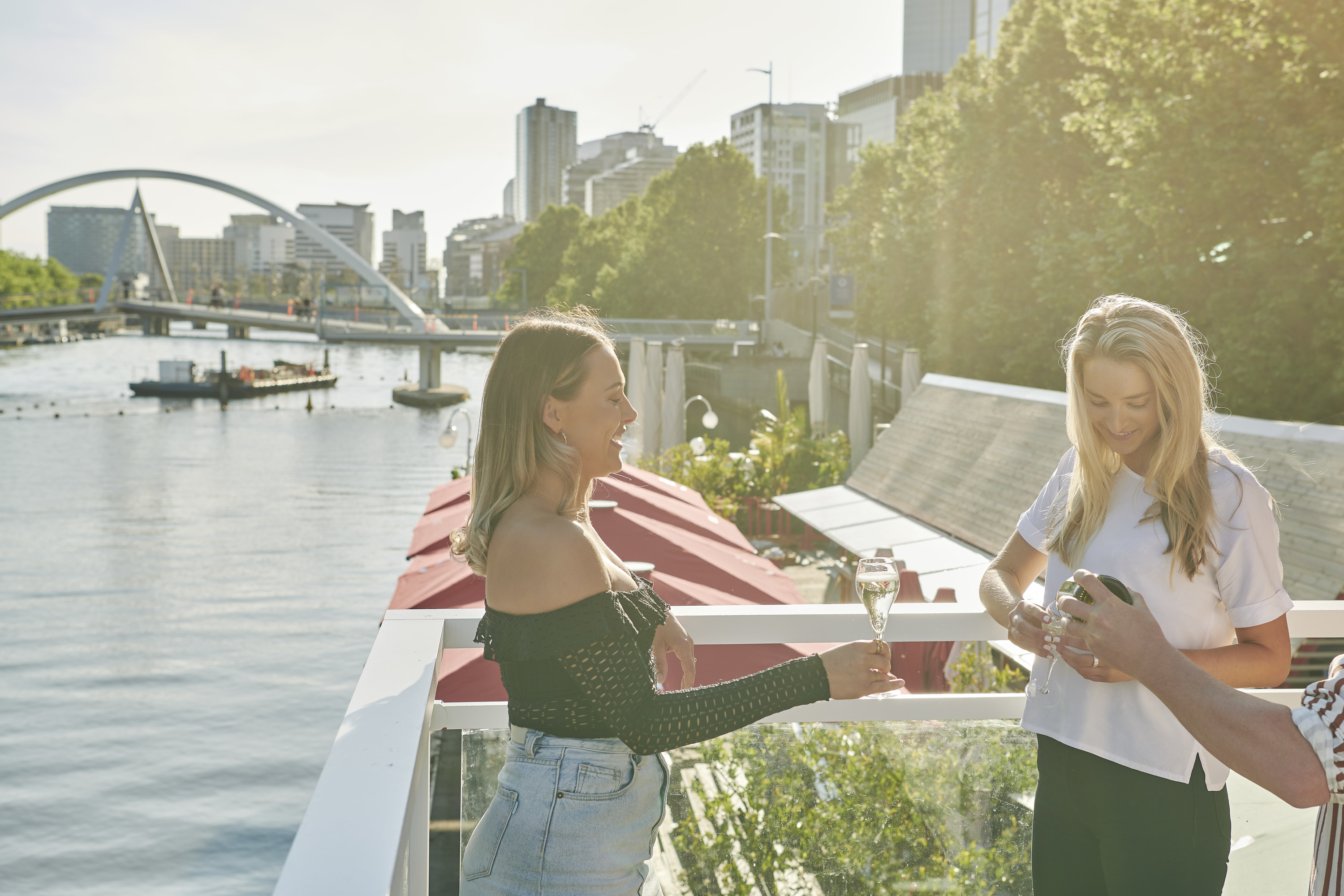 Two women at Arbory Afloat drinking sparkling wine over the Yarra River.