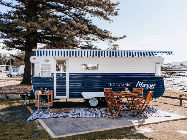 A vintage caravan parked by the ocean with a cocktail trolley
