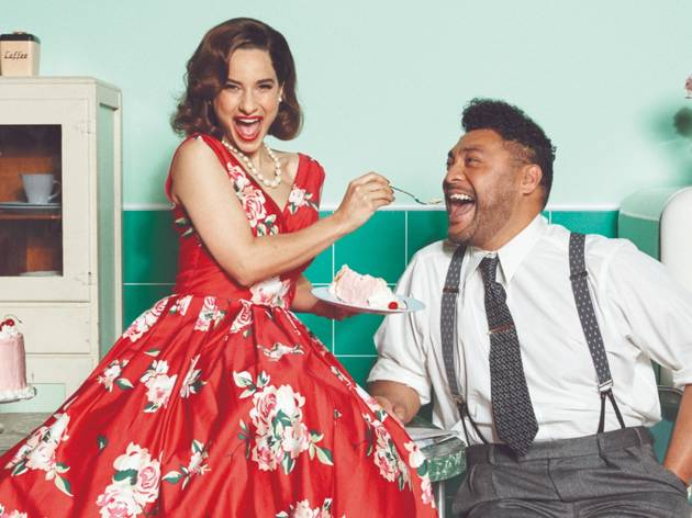 Andrea Demetriades in a 1950s dress feeds cake to Anthony Taufa in shirt, tie and braces