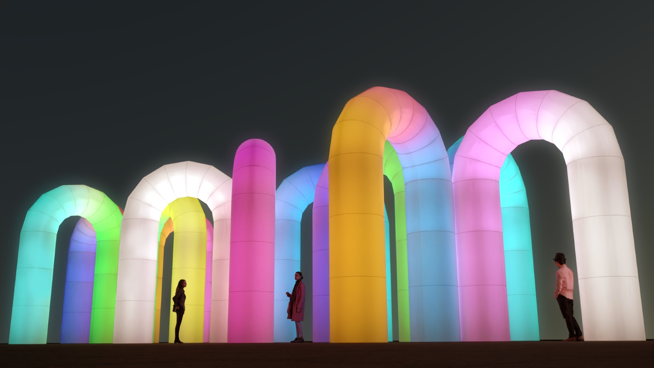 People standing underneath giant, glowing rainbow inflatable arches