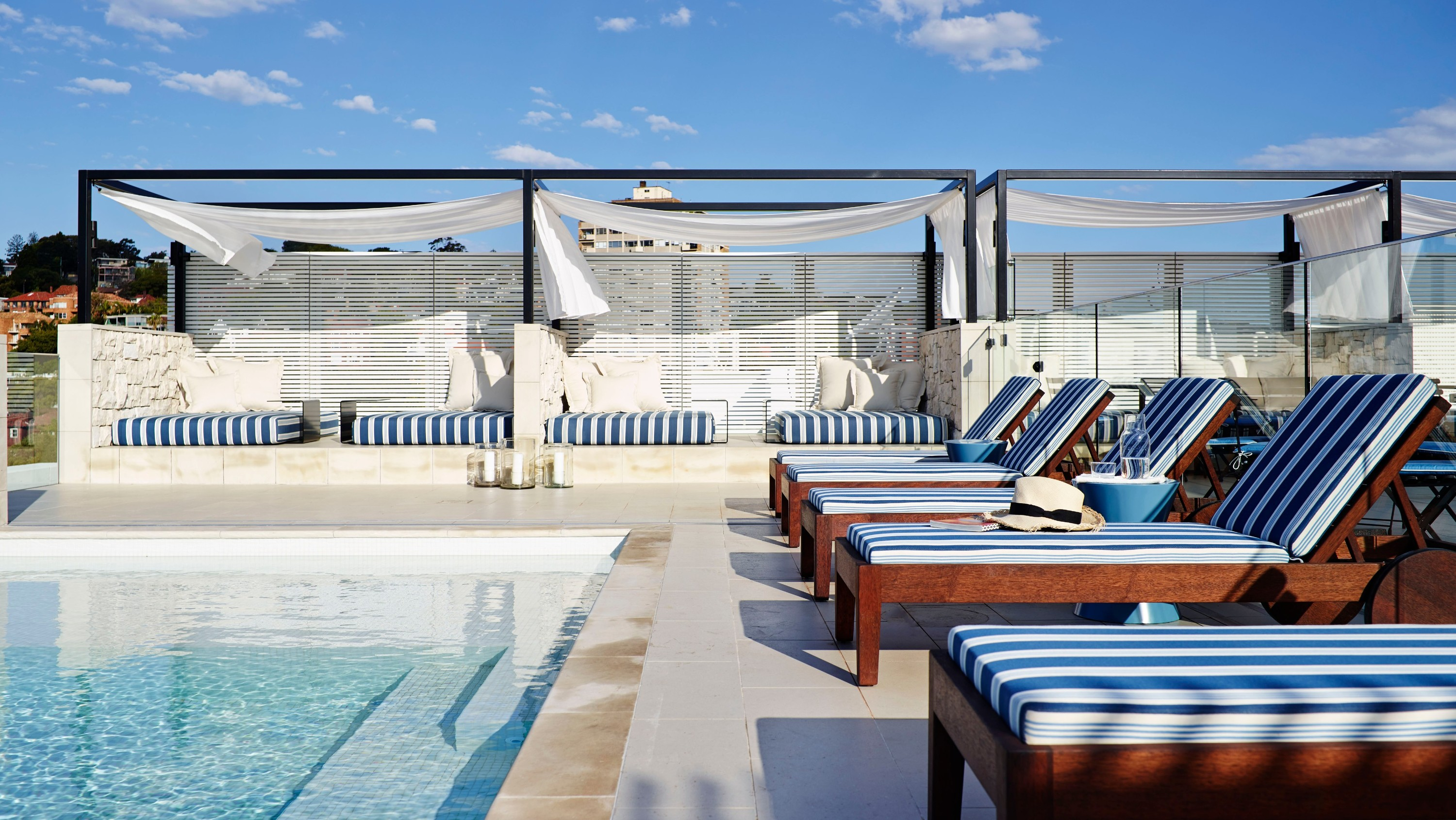 Rooftop pool with loungers next to it