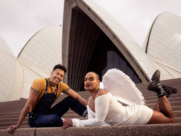 Callum Francis and Seann Miley Moore in costume for Rent, including angel wings, on the steps of the Opera House