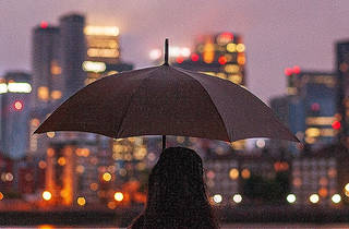 The silhouette of a person under an umbrella starting at Melbourne city around twilight