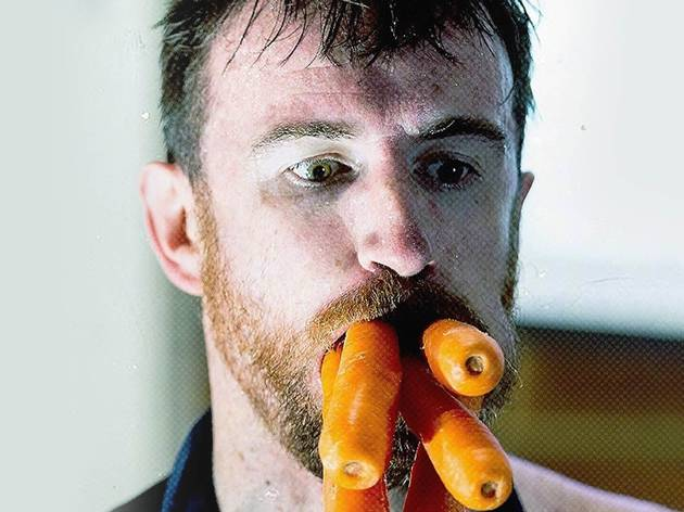 A man's face with five whole carrots sticking out of his mouth