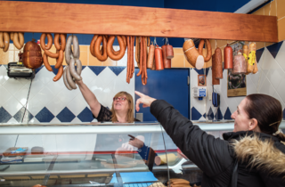 Two ladies in a deli. One pointing at cured sausages, other being the deli assistant picking it out for her.