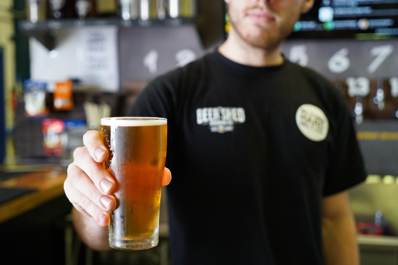 Bartender holds a beer.