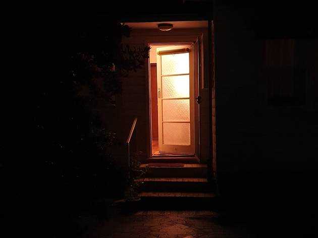 A lit doorway surrounded by darkness