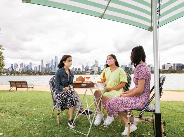 Three ladies sitting on chairs by a table with wine, beers and food under an umbrella. View behind is the city's skyline and lake.