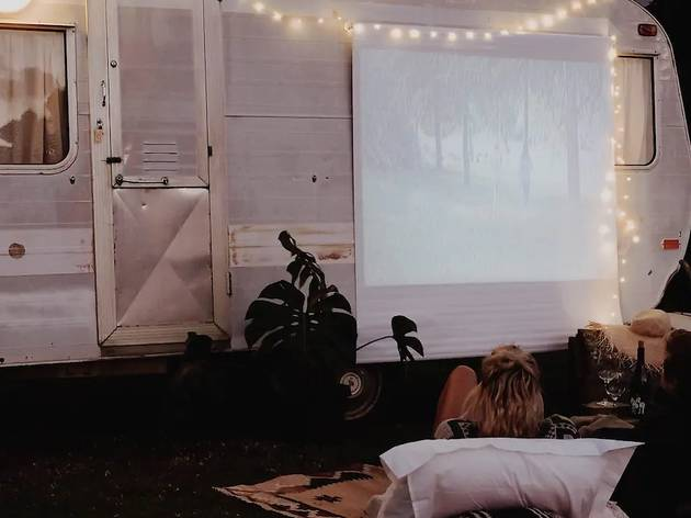 Two people sitting in front of a projector screen on a caravan
