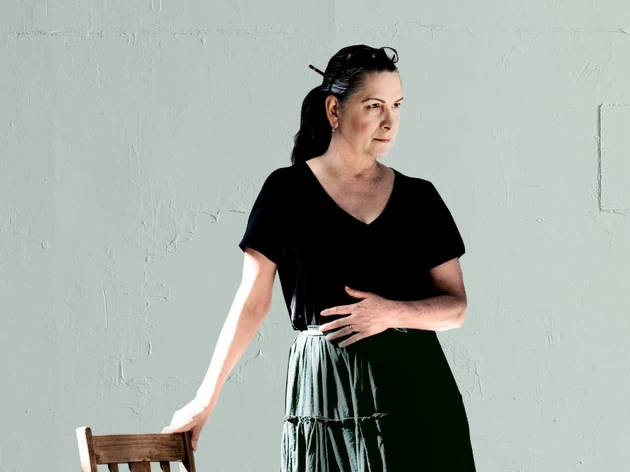 Pamela Rabe in a black dress leans on a wooden chair in The Cherry Orchard at Belvoir