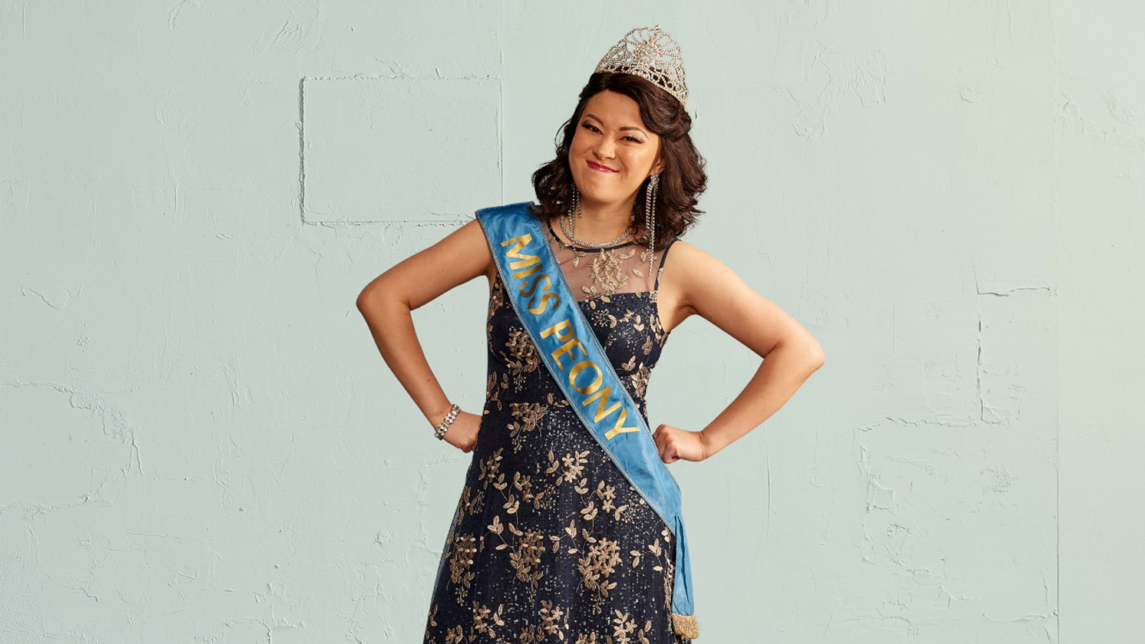 Michelle Law in blue winners sash, tiara and navy patterned dress in Miss Peony