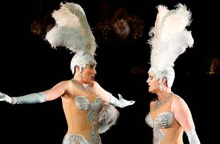 Two performers wear bejwelled light blue costumes with feathered head pieces.