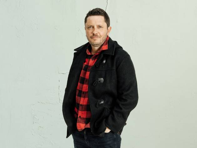 At What Cost? playwright Nathan Maynard in a red flannel shirt and a navy duffel coat