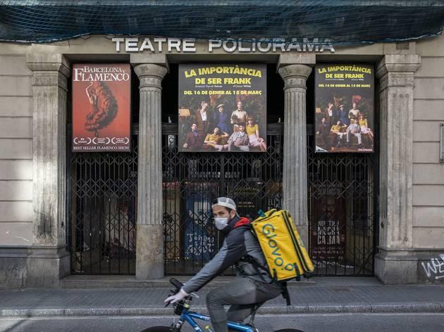 Un repartidor de Glovo passa davant del Teatre Poliorama tancat