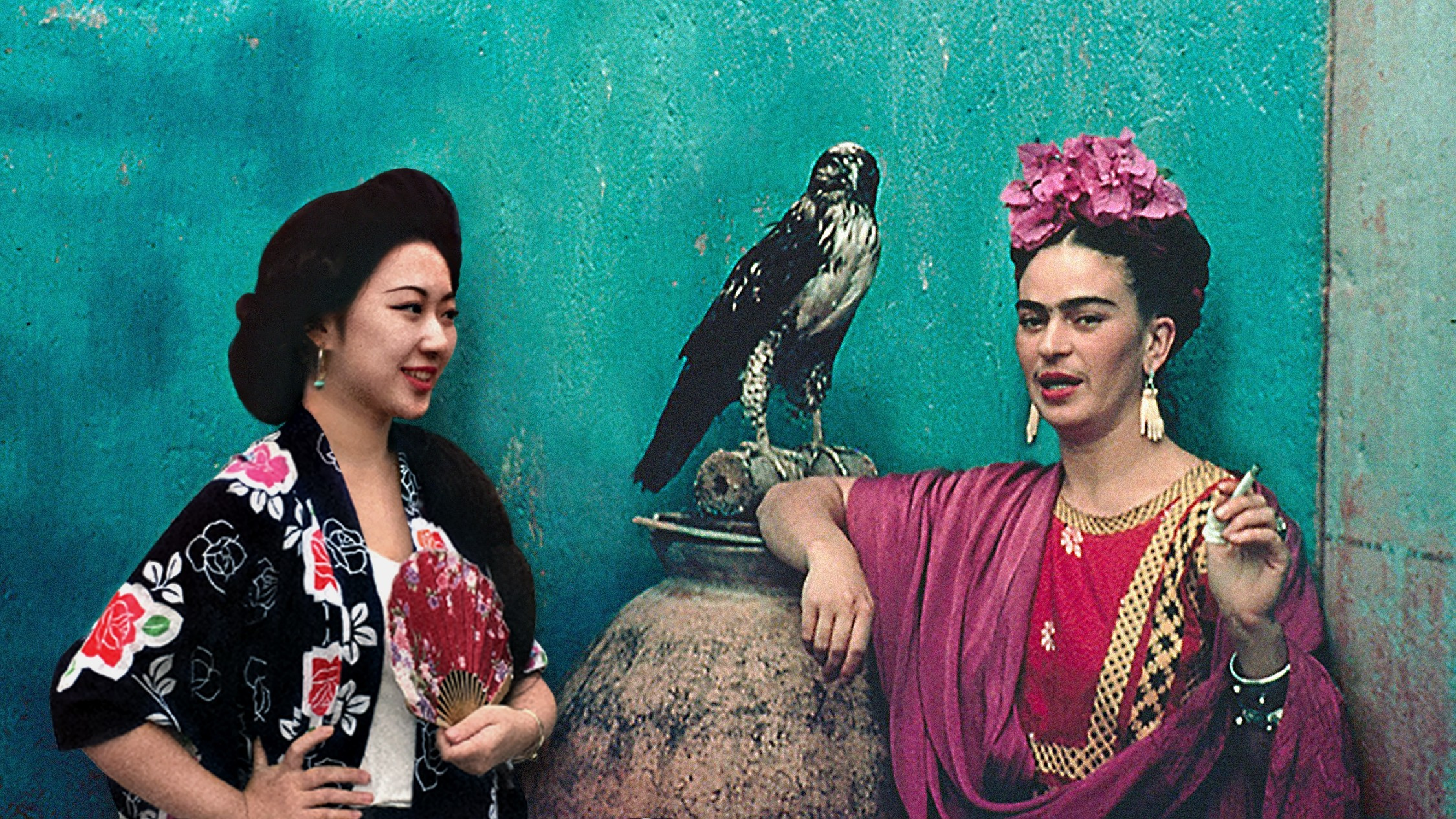 A photograph of two women, one of which is Frida Kahlo, standing against a bright teal wall. A hawk rests on a man-sized vase behind them