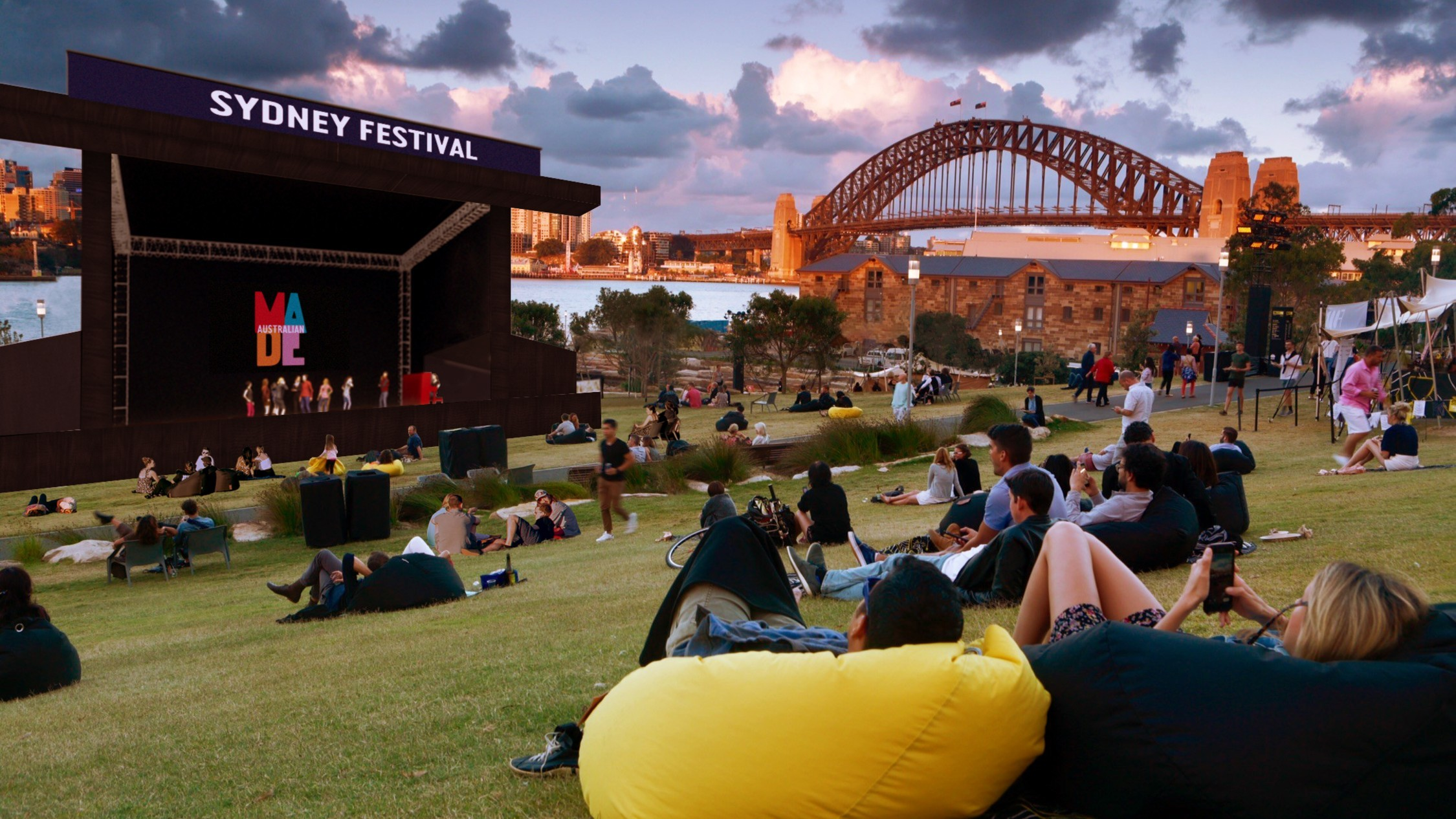 People lounge on beanbags at Barangaroo looking out to a Sydney Festival stage with the Harbour Bridge in the background