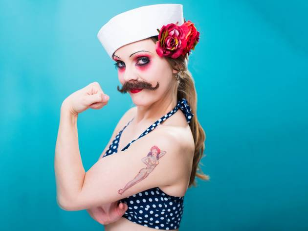 A woman with a moustache in a polka dot bikini top and sailors hat flexes her guns