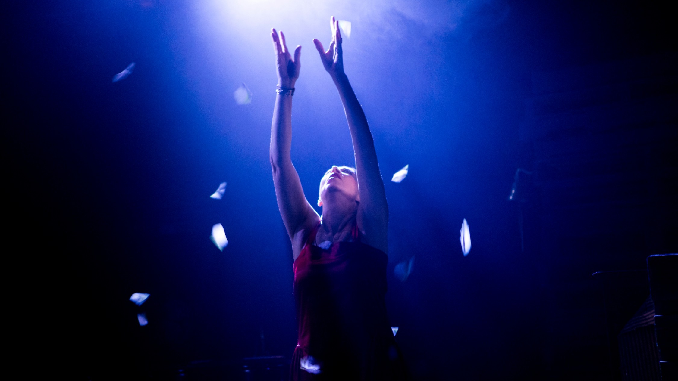 A woman in a red sleeveless top reaches or a light in the dark as feathers float down