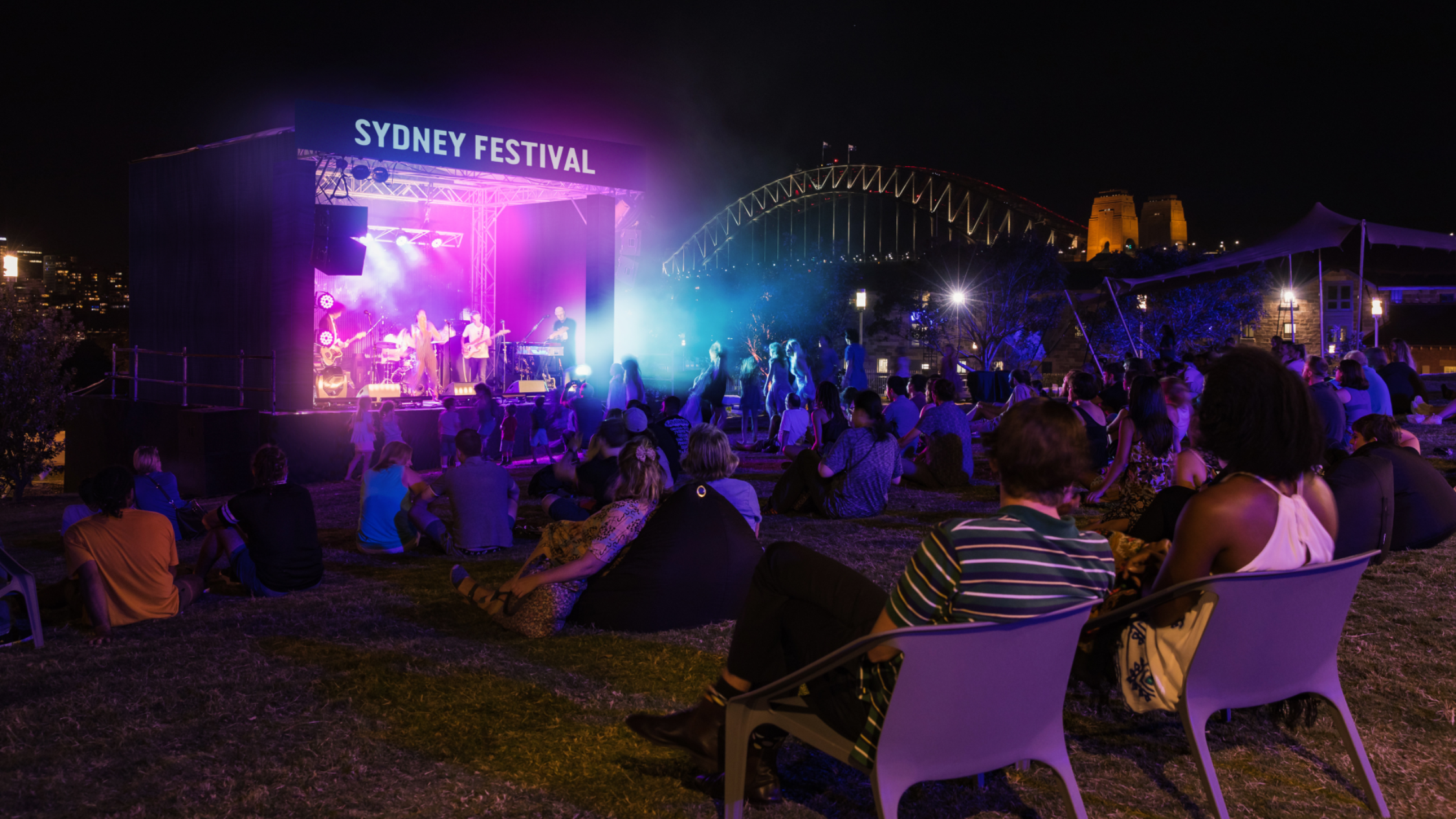 A night time view of the Sydney Festival 2021Barangaroo Headlands stage with the Harbour Bridge in the background