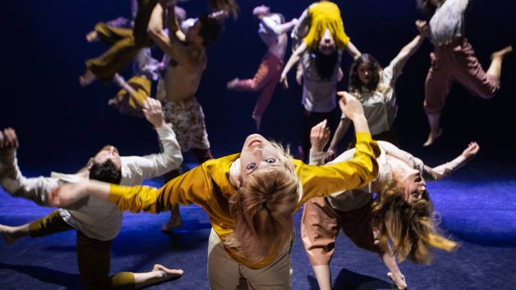 a circle of people in bright yellow tops mid-leap