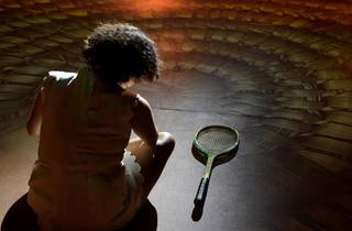 Image from behind of Katie Beckett playing Wiradjuri woman and tennis legend Evonne Goolagong lookig at her racket on the ground