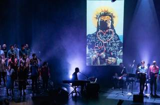 A performance of The Rise and Fall of Saint George, with a choir on stage, Paul Mac playing keyboard, and a projected mural of George Michael