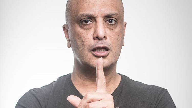 Comedian Akmal stares down the camera with his finger raised.