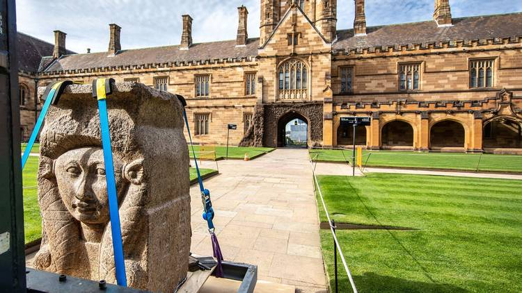 A granite statue of the Ancient Egyptian goddess Hera is strapped to a trolley and being moved across the grounds of the University of Sydney.