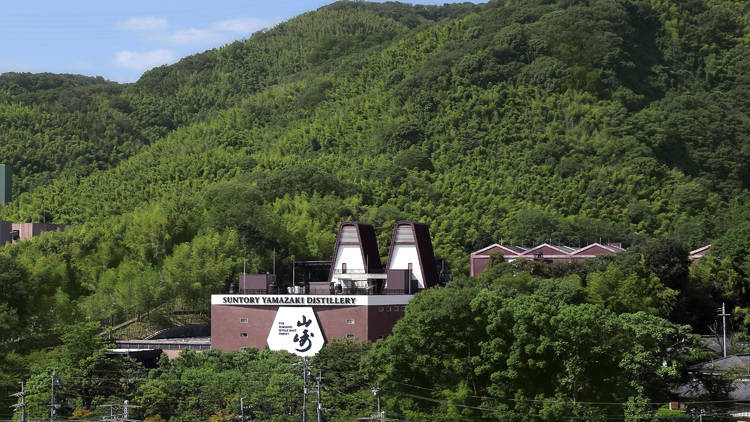 A red and white brick distillery building at the foot of a hill covered in green trees