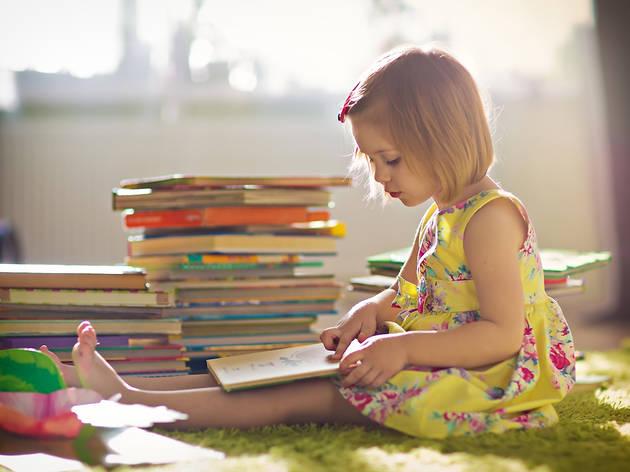Nena llegint llibres infantils