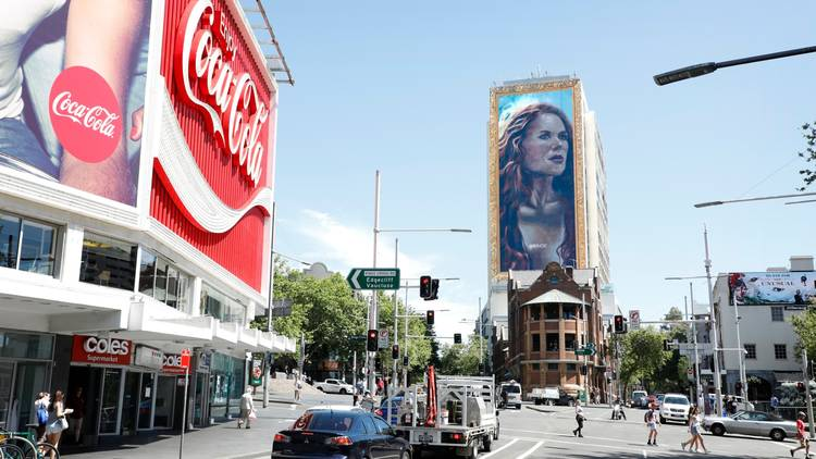 A huge mural of Nicoel Kidman on the side of a building opposite the Coca-Cola sing in the Cross