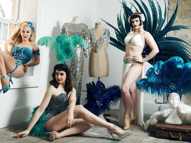 Three performers pose in glittering outfits with feather head dresses and costumes on mannikins.