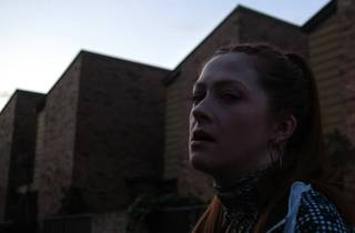A woman stands in front of brick warehouses
