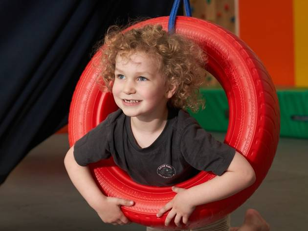 Five year old playing in a tyre swing