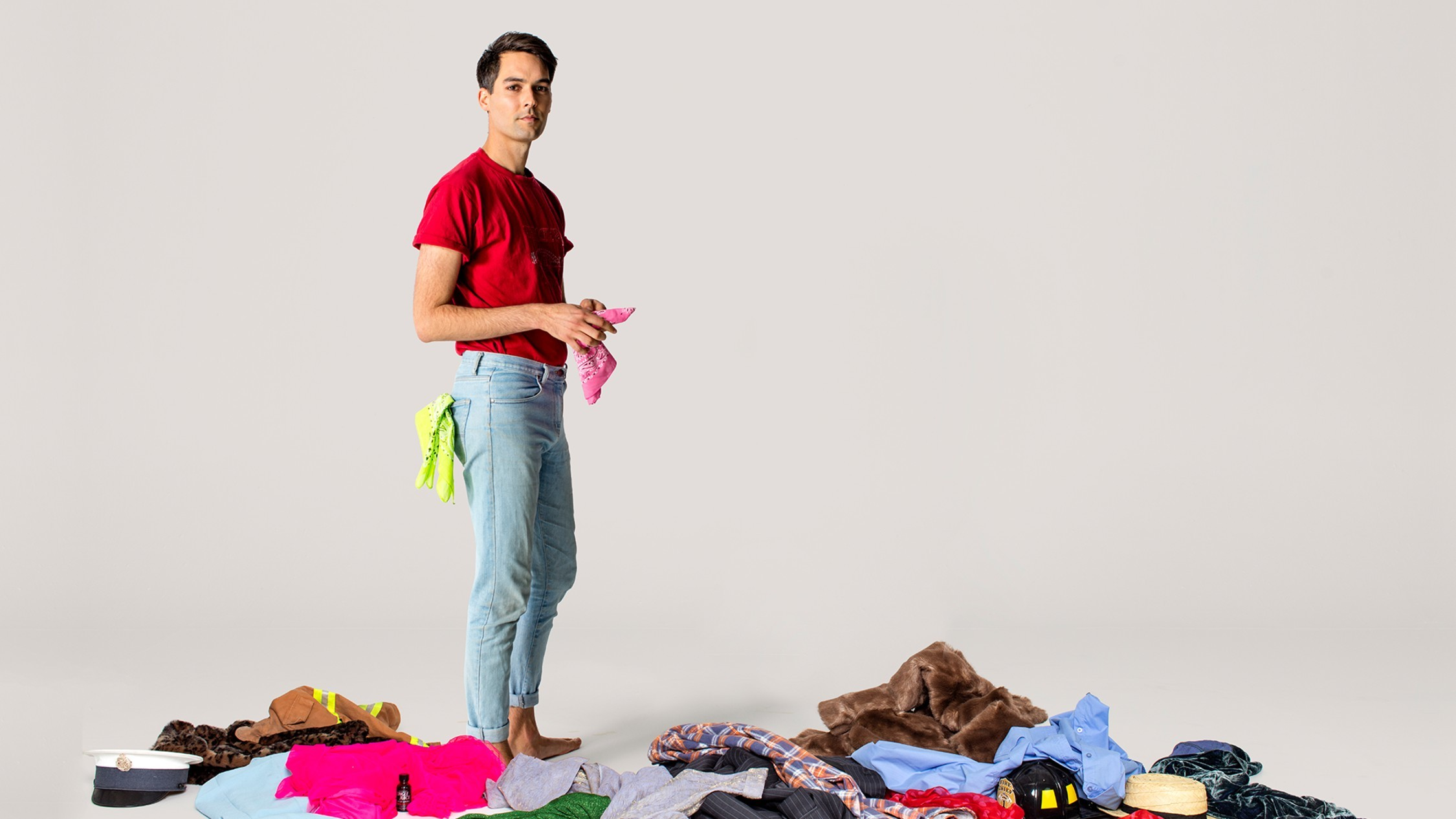 A man in jean and a red t-shirt stands in a pile of clothes