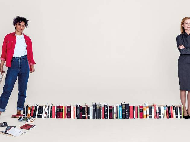A young woman in jeans and red shirt and an older woman in a dark grey twin suit with a row of books on the floor between them