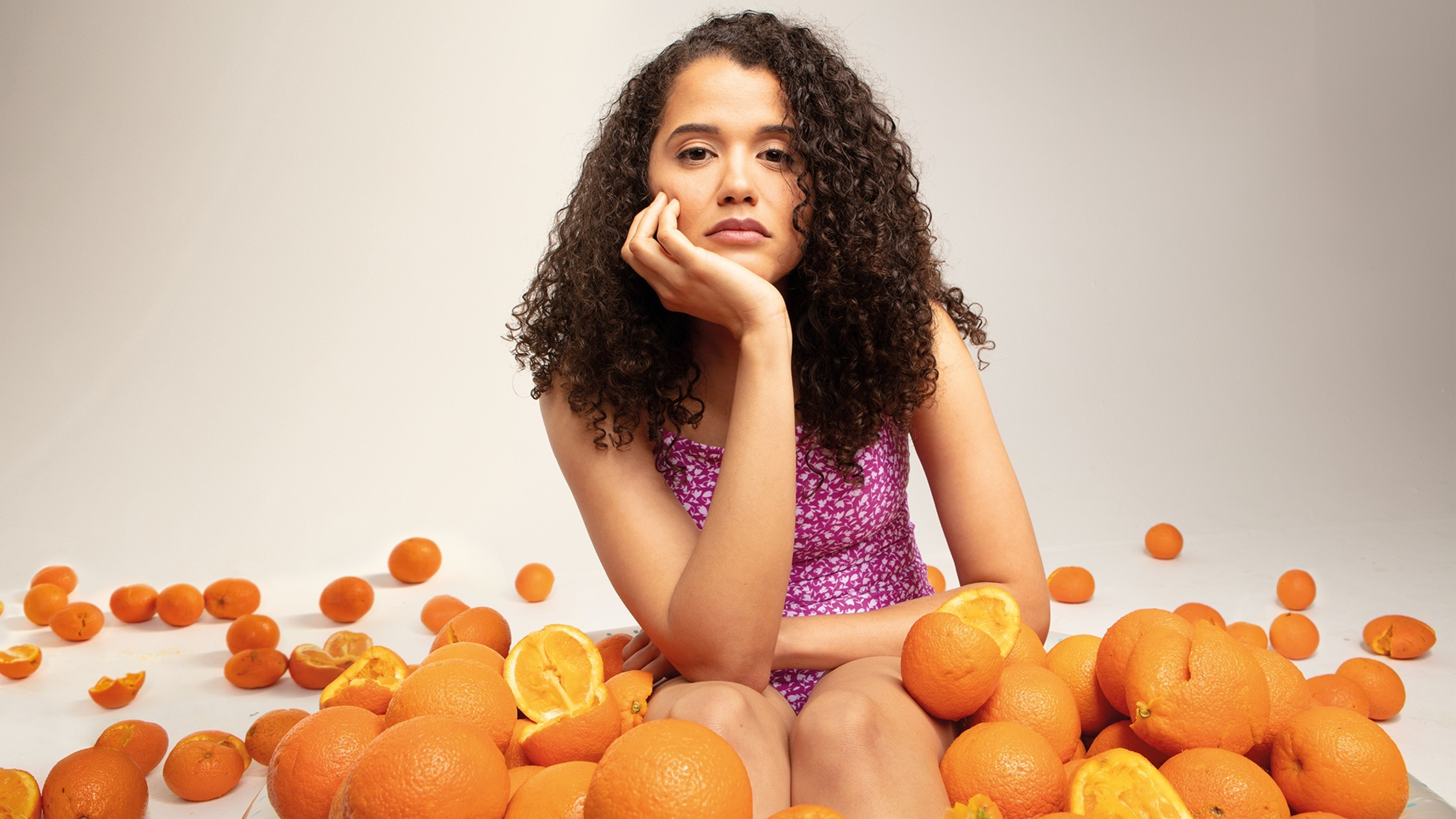 A woman in a pink dress sits in a pile of oranges, some cut in half