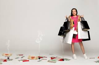 A girl ini a pink dress clutching shopping bags with incense smoking all around her