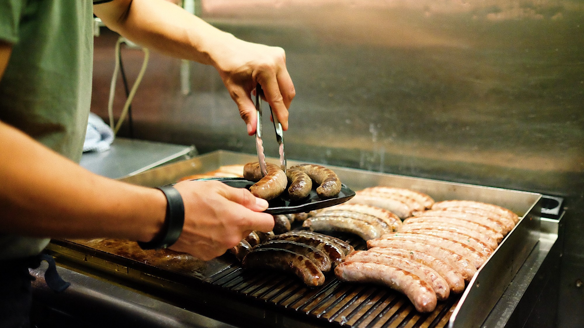 Person fills plate with sausages from industrial grill with rows of sausages.