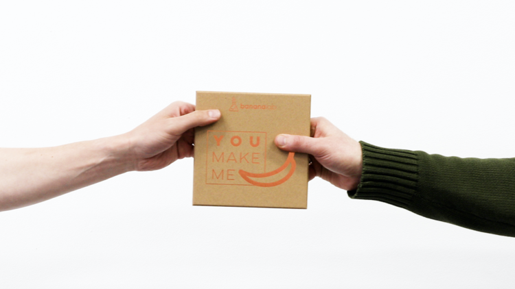 Two hands holding a BananaLab gift box on a white background