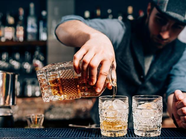 Pouring Old Fashioned cocktails