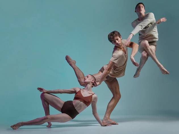 Three dancers one on the floor, one standing, one mid-leap, forming a chain against a blue backdrop