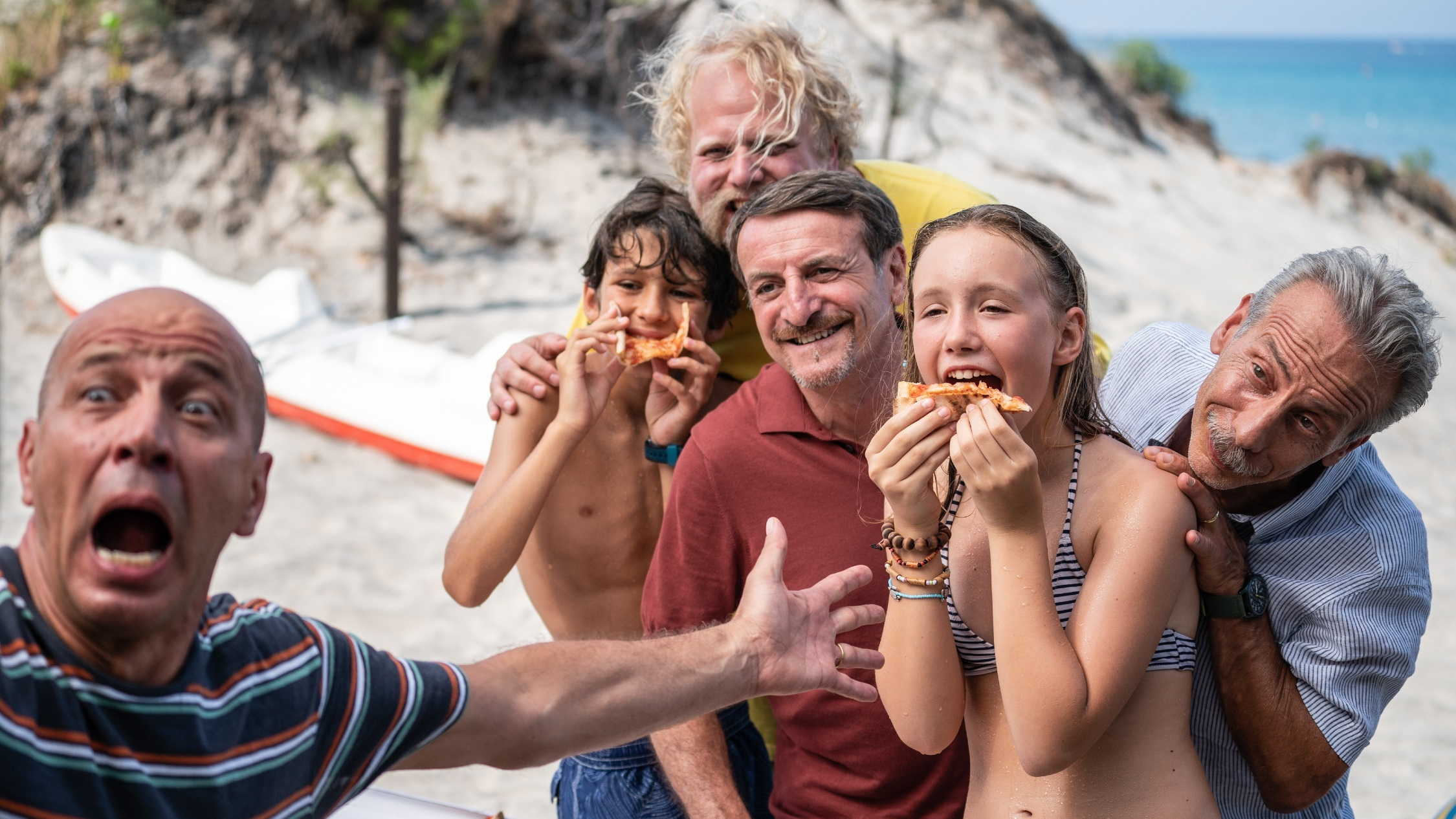 A family eating pizza on a beach while a man in the foreground gestures a them wildly