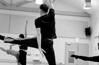 Three dancers rehearsing, shot in studio from behind