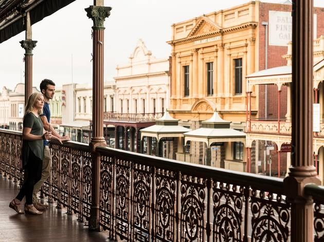 Two people standing on a balcony on Lydiard Street in Ballarat