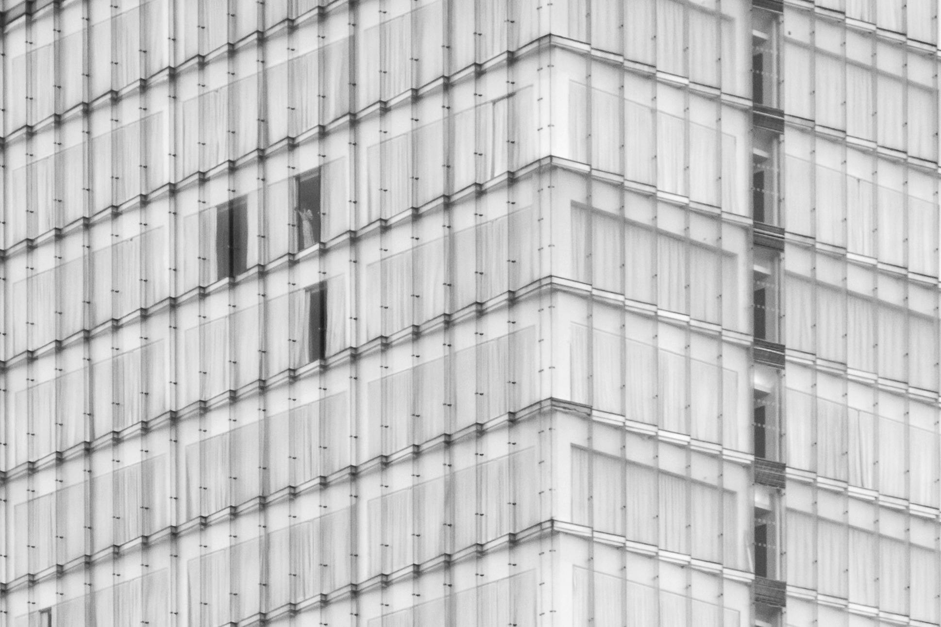 Imagen de ventanas en edificio alto con una persona asomándose por la ventana