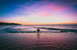 Two people silhouetted at Bronte pool at sunset